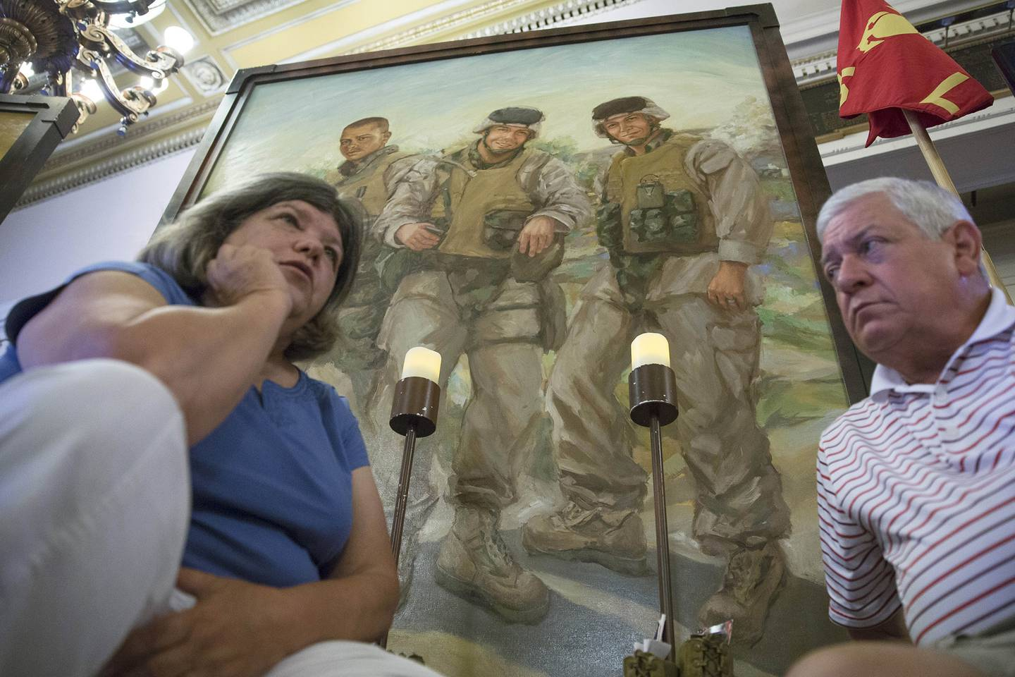 In this file photo from July 28, 2015, Pat Murray, left, and Ken Kreuter sit beneath a portrait of their son Marine Sgt. David Kreuter, top right, at the traveling Eyes of Freedom Lima Company Memorial, then displayed at the Cincinnati Masonic Center.