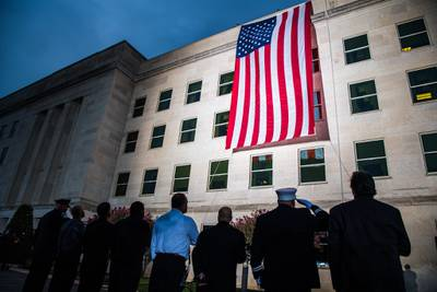 A Pentagon crew unfurls an American flag at dawn on the 18th anniversary of the 9/11 attacks at the Pentagon, Sept. 11, 2019.