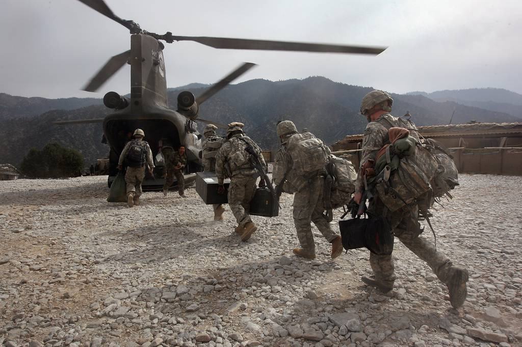 U.S. soldiers board an Army Chinook transport helicopter in Afghanistan, surrounded by mountain peaks.
