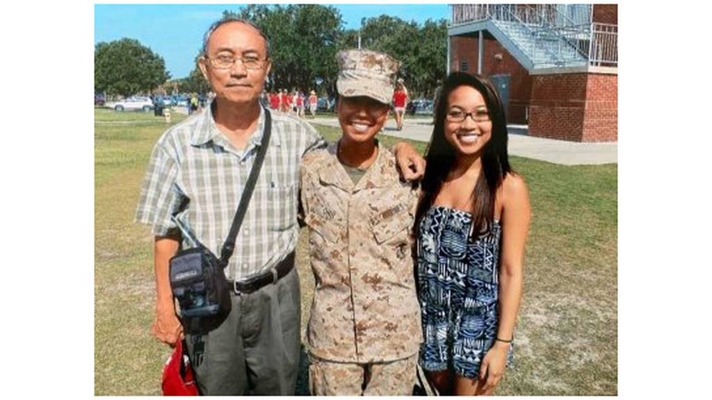 Ohu, center, stands with her father Ahr Yu, left, and sister Kay Yu after she earns the title of Marine.