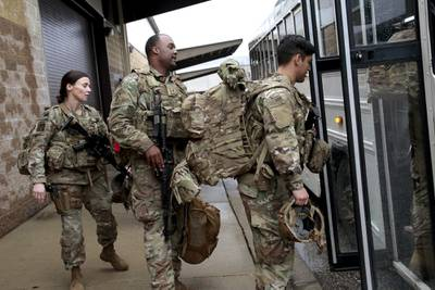In this Jan. 4, 2020, file photo, U.S. Army soldiers with their gear board an awaiting bus at Fort Bragg, N.C., as troops from the 82nd Airborne are deployed to the Middle East.