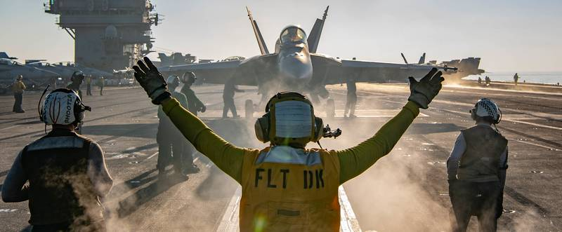 A sailor directs an F/A-18E Super Hornet on the flight deck of the aircraft carrier USS Nimitz (CVN 68) during flight operations on Jan. 17, 2021, in the Arabian Sea.