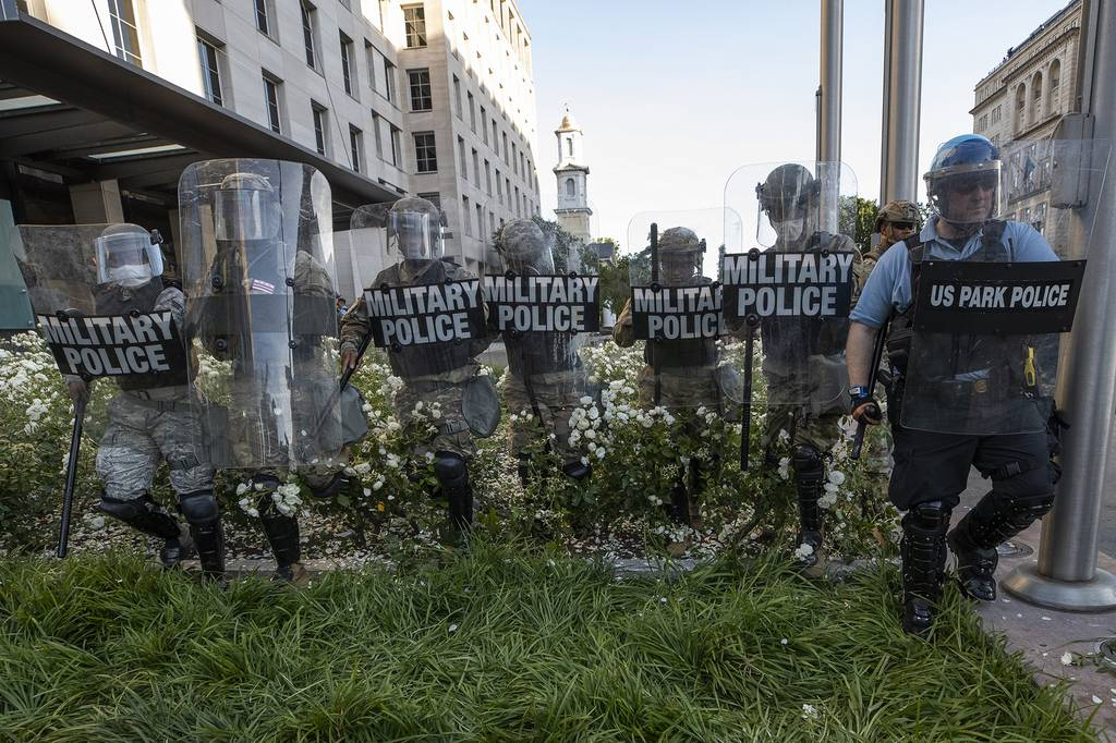 In this June 1, 2020, file photo, District of Columbia National Guard, and U.S. Park Police, advance through the white roses in front of the AFL-CIO headquarters, with St. John's Church behind them, as they move demonstrators back after they gathered to protest the death of George Floyd near the White House in Washington.
