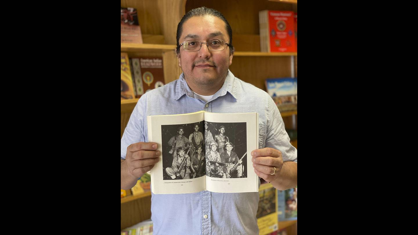 This Nov. 8, 2019, photo shows LT Goodluck holding a book with a photo of his grandfather, John V. Goodluck, first row, third from left holding a machine gun, with other Navajo Code Talkers at the Navajo Museum in Window Rock, Ariz.